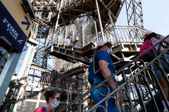 Visitors wearing protective facemasks walk up the stairs to the second floor as they visit the Eiffel Tower during its partial reopening on June 25, 2020, in Paris, as France eases lockdown measures taken to curb the spread of the COVID-19 caused by the novel coronavirus. - Tourists and Parisians will again be able to admire the view of the French capital from the Eiffel Tower after a three-month closure due to the coronavirus -- but only if they take the stairs. (Photo by Thomas SAMSON / AFP) (Photo by THOMAS SAMSON/AFP via Getty Images)