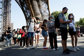 Visitors wearing protective facemasks queue as they wait for the partial reopening of Eiffel Tower on June 25, 2020, in Paris, as France eases lockdown measures taken to curb the spread of the COVID-19 caused by the novel coronavirus. - Tourists and Parisians will again be able to admire the view of the French capital from the Eiffel Tower after a three-month closure due to the coronavirus -- but only if they take the stairs. (Photo by Thomas SAMSON / AFP) (Photo by THOMAS SAMSON/AFP via Getty Images)