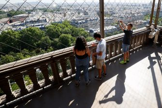 Visitors wearing protective facemasks admire and take pictures of the view from the Eiffel Tower during its partial reopening on June 25, 2020, in Paris, as France eases lockdown measures taken to curb the spread of the COVID-19 caused by the novel coronavirus. - Tourists and Parisians will again be able to admire the view of the French capital from the Eiffel Tower after a three-month closure due to the coronavirus -- but only if they take the stairs. (Photo by Thomas SAMSON / AFP) (Photo by THOMAS SAMSON/AFP via Getty Images)