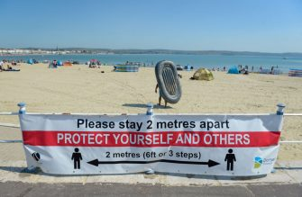 WEYMOUTH, ENGLAND - JUNE 24: A coronavirus social distancing warning sign is displayed at the beach on June 24, 2020 in Weymouth, United Kingdom. The UK is experiencing a summer heatwave, with temperatures in many parts of the country expected to rise above 30C and weather warnings in place for thunderstorms at the end of the week. (Photo by Finnbarr Webster/Getty Images)