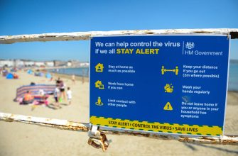 WEYMOUTH, ENGLAND - JUNE 24: A coronavirus warning sign is displayed at the beach on June 24, 2020 in Weymouth, United Kingdom. The UK is experiencing a summer heatwave, with temperatures in many parts of the country expected to rise above 30C and weather warnings in place for thunderstorms at the end of the week. (Photo by Finnbarr Webster/Getty Images)