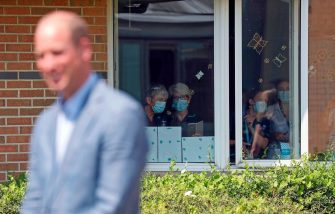 People wearing PPE (personal protective equipment), of a face mask or covering as a precautionary measure against spreading COVID-19, watch from a a window as Britain's Prince William, Duke of Cambridge talks to staff at Oxford Vaccine Group's facility at Churchill Hospital in Oxford, west of London on June 24, 2020, during a visit to learn more about the group's work to establish a viable vaccine against the novel coronavirus COVID-19. (Photo by Steve Parsons / POOL / AFP) (Photo by STEVE PARSONS/POOL/AFP via Getty Images)