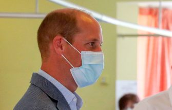 Britain's Prince William, Duke of Cambridge, wearing PPE (personal protective equipment), of a face mask or covering as a precautionary measure against spreading COVID-19, talks to a patient (unseen) participating in a COVID-19 vaccine trial at Oxford Vaccine Group's facility at Churchill Hospital in Oxford, west of London on June 24, 2020, during a visit to learn more about their work to establish a viable vaccine against coronavirus. (Photo by Steve Parsons / POOL / AFP) (Photo by STEVE PARSONS/POOL/AFP via Getty Images)