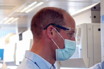 Britain's Prince William, Duke of Cambridge, wearing PPE (personal protective equipment), of a face mask or covering, eye protection and an overall, as a precautionary measure against spreading COVID-19, meets scientists during a visit to the manufacturing laboratory where a vaccine against the novel coronavirus COVID-19 has been produced at the Oxford Vaccine Group's facility at the Churchill Hospital in Oxford, west of London on June 24, 2020, during a visit to learn more about their work to establish a viable vaccine against coronavirus. (Photo by Steve Parsons / POOL / AFP) (Photo by STEVE PARSONS/POOL/AFP via Getty Images)
