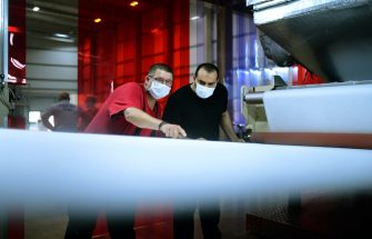 Workers check the quality of non-woven fabric, produced for protective masks at the Innovatec production facility in Troisdorf, western Germany on June 25, 2020. - The North Rhine-Westphalian company intends to produce an additional 1500 tons of nonwoven matrial per year in the future with the two newly installed subsidized meltblown lines. The additional volume will enable the production of more than 1.5 billion protective masks. (Photo by Ina FASSBENDER / AFP) (Photo by INA FASSBENDER/AFP via Getty Images)