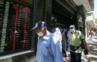 Iranians, wearing protective masks due to the COVID-19 pandemic, wait outside a money exchange office in the capital Tehran, on June 22, 2020. (Photo by ATTA KENARE / AFP) (Photo by ATTA KENARE/AFP via Getty Images)