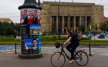 KRAKOW, POLAND - JUNE 26: A woman drives a bicycle next to campaign posters of Rafal Trzaskowski, the Mayor of Warsaw and presidential candidate for the centre-right main opposition party, Civic Coalition (KO) and the incumbent President, Andrzej Duda on the last campaign day before Sunday's Presidential elections on June 26, 2020 in Krakow, Poland. Recent polling suggests current President Andrzej Duda may not claim enough votes to win in the first round, and could face a run-off election with Warsaw's liberal mayor, Rafal Trzaskowski. (Photo by Omar Marques/Getty Images)