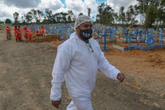 Brazilian evangelical pastor Izaias Nascimento, 49, walks at the Sao Francisco cemetery, in Manaus, Amazonas state, Brazil, on June 5, 2020. - Nascimento, during the day, provides funeral services to families with low budget who need to bury their loved ones, most of them victims of new coronavirus, and at night, he gives comfort in times of pandemic as a pastor. (Photo by MICHAEL DANTAS / AFP) (Photo by MICHAEL DANTAS/AFP via Getty Images)