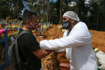 Brazilian evangelical pastor Izaias Nascimento (R), 49, comforst with Luiz Hernandes (L), during his father's funeral, at the Sao Francisco cemetery, in Manaus, Amazonas state, Brazil, on June 5, 2020, amid the new coronavirus pandemic. - Nascimento, during the day, provides funeral services to families with low budget who need to bury their loved ones, most of them victims of new coronavirus, and at night, he gives comfort in times of pandemic as a pastor. (Photo by MICHAEL DANTAS / AFP) (Photo by MICHAEL DANTAS/AFP via Getty Images)