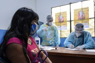 Brazilian indigenous Anita, of the Marubo ethnic group, is notified that she contracted the new coronavirus by a member of the medical team of the Brazilian Armed Forces at health post in Atalaia do Norte, Amazonas state, northern Brazil, on the border with Peru, on June 20, 2020. - As the new coronavirus has ravaged Brazil, more than 7,000 indigenous people have contracted the virus, and more than 300 have died, according to the Brazilian Indigenous Peoples' Association (APIB), forcing many indigenous groups to take matters into their own hands. Some have locked the world out, banning outsiders and putting up a makeshift roadblock at the entrance to their territory, while others have fled into the jungle. (Photo by EVARISTO SA / AFP) (Photo by EVARISTO SA/AFP via Getty Images)