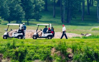 epa08512910 US President Donald J. Trump (R) plays golf at the Trump National Golf Club in Sterling, Virginia, USA, 27 June 2020. On 26 June, Trump abruptly canceled a weekend trip to Bedminster, NJ, tweeting that he 'wanted to stay in Washington, D.C. to make sure LAW & ORDER is enforced.'  EPA/JIM LO SCALZO