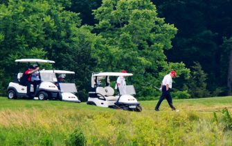 epa08512905 US President Donald J. Trump (R) plays golf at the Trump National Golf Club in Sterling, Virginia, USA, 27 June 2020. On 26 June, Trump abruptly canceled a weekend trip to Bedminster, NJ, tweeting that he 'wanted to stay in Washington, D.C. to make sure LAW & ORDER is enforced.'  EPA/JIM LO SCALZO