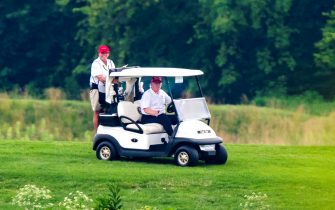 epa08512909 US President Donald J. Trump drives a golf cart after playing golf at the Trump National Golf Club in Sterling, Virginia, USA, 27 June 2020. On 26 June, Trump abruptly canceled a weekend trip to Bedminster, NJ, tweeting that he 'wanted to stay in Washington, D.C. to make sure LAW & ORDER is enforced.'  EPA/JIM LO SCALZO