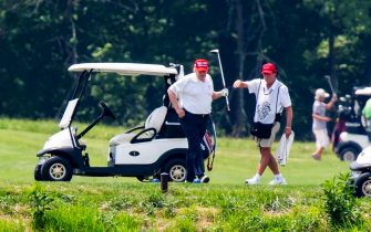 epa08512915 US President Donald J. Trump (C) plays golf at the Trump National Golf Club in Sterling, Virginia, USA, 27 June 2020. On 26 June, Trump abruptly canceled a weekend trip to Bedminster, NJ, tweeting that he 'wanted to stay in Washington, D.C. to make sure LAW & ORDER is enforced.'  EPA/JIM LO SCALZO