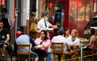 NEW YORK, NEW YORK - JUNE 26: Customers dine outside Via Carota restaurant in the West Village as New York City moves into Phase 2 of re-opening following restrictions imposed to curb the coronavirus pandemic on June 26, 2020. Phase 2 permits the reopening of offices, in-store retail, outdoor dining, barbers and beauty parlors and numerous other businesses. Phase 2 is the second of four-phased stages designated by the state. (Photo by Noam Galai/Getty Images)