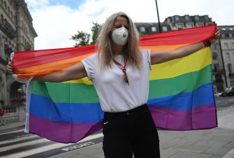 epa08512155 A person holds a Rainbow flag during a reduced Pride March in London, Britain, 27 June 2020. Former members of London's Gay Liberation Front are marking the organization's 50th birthday by marching the route of cancelled pride parade. The GLF protest also supports Black Lives Matter movement and the LGBTQ+ people.  EPA/NEIL HALL