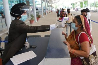 An airport staff checks the body temperature of a passenger at Sri Guru Ram Dass Jee International Airport as domestic flights resumed after the government eased a lockdown imposed as a preventive measure against the spread of the COVID-19 coronavirus, on the outskirts of Amritsar on Amritsar on May 25, 2020. - Domestic flights resumed in India on May 25 even as coronavirus cases surge, while confusion about quarantine rules prompted jitters among passengers and the cancellation of dozens of planes. (Photo by NARINDER NANU / AFP) (Photo by NARINDER NANU/AFP via Getty Images)