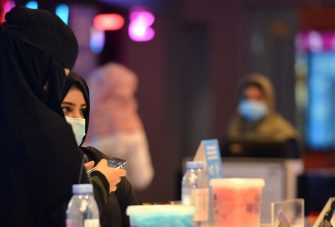 Saudi women buy tickets for a movie at a cinema in the capital Riyadh, on June 22, 2020 as cinemas re-opened following the lifting of a lockdown due to the COVID-19 coronavirus pandemic. (Photo by FAYEZ NURELDINE / AFP) (Photo by FAYEZ NURELDINE/AFP via Getty Images)
