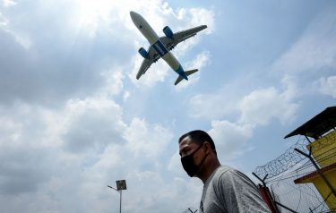 A Jazeera Airways plane approaches to land while a man wearing a facemask as a preventive measure against the spread of the COVID-19 coronavirus walks under at the Tribhuvan International airport in Kathmandu on June 11, 2020. (Photo by PRAKASH MATHEMA / AFP) (Photo by PRAKASH MATHEMA/AFP via Getty Images)