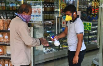 A shopkeeper sprays sanitiser in the hands of a customer before entering a grocery shop during the first day of a 21-day government-imposed nationwide lockdown as a preventive measure against the COVID-19 coronavirus, in Mumbai on March 25, 2020. - India's billion-plus population went into a three-week lockdown on March 25, with a third of the world now under orders to stay indoors, as the coronavirus pandemic forced Japan to postpone the Olympics until next year. (Photo by INDRANIL MUKHERJEE / AFP) (Photo by INDRANIL MUKHERJEE/AFP via Getty Images)