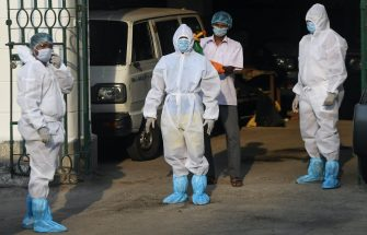 A municipal worker sprays disinfectant on a colleague after returning from cremating the body of a suspected coronavirus patient on a hearse during a government-imposed nationwide lockdown as a preventive measure against the COVID-19 coronavirus, in Kolkata on  April 19, 2020. (Photo by Dibyangshu SARKAR / AFP) (Photo by DIBYANGSHU SARKAR/AFP via Getty Images)