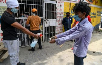A shopkeeper (L) sprays disinfectant on customers' hands as they queue to buy alcohol from government-run liquor shops after the government eased a nationwide lockdown imposed as a preventive mearure against the COVID-19 coronavirus, in Ghaziabad on May 6, 2020. (Photo by Prakash SINGH / AFP) (Photo by PRAKASH SINGH/AFP via Getty Images)