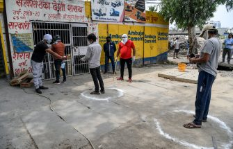 TOPSHOT - A shopkeeper (L) sprays disinfectant on customers' hands as they queue standing in marked circles to buy alcohol from government-run liquor shops after the government eased a nationwide lockdown imposed as a preventive mearure against the COVID-19 coronavirus, in Ghaziabad on May 6, 2020. (Photo by Prakash SINGH / AFP) (Photo by PRAKASH SINGH/AFP via Getty Images)