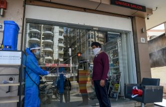 A worker (L) wearing protective gear as a precautionary measure against the COVID-19 coronavirus sprays disinfectant on a customer before entering a hair and beauty salon located in an area declared as green zone for the pandemic, in Nadiad some 50 kms from Ahmedabad on May 17, 2020. (Photo by SAM PANTHAKY / AFP) (Photo by SAM PANTHAKY/AFP via Getty Images)