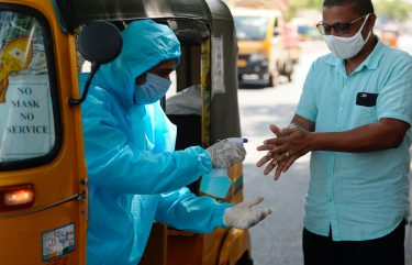 An auto rickshaw driver wearing personal protective equipments (PPE) sprays sanitiser on the hands of a customer after the government eased a nationwide lockdown imposed as a preventive measure against the COVID-19 coronavirus, in Chennai on June 2, 2020. (Photo by Arun SANKAR / AFP) (Photo by ARUN SANKAR/AFP via Getty Images)