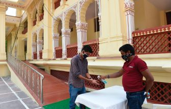 A volunteer (R) from the International Society for Krishna Consciousness (ISKCON) temple sprays sanitiser to a Hindu devotee who arrived to offer prayers, after the government eased a lockdown imposed as a preventive measure against the COVID-19 coronavirus, in Ahmedabad on on June 8, 2020. - Malls and temples re-opened in several cities across India on June 8 despite the country recording a record daily number of new coronavirus infections, with the pandemic expected to ravage the country for weeks to come. (Photo by SAM PANTHAKY / AFP) (Photo by SAM PANTHAKY/AFP via Getty Images)
