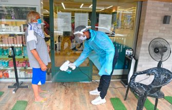 Staff at Shiva's Signature hair salon sprays disinfectant to a customer at the entrance after personal grooming services were allowed to resume following relaxation of lockdown norms amidst Covid-19 coronavirus pandemic, in Mumbai on June 28, 2020. - India now has more than 500,000 confirmed coronavirus cases, according to government figures released on June 27 that showed a record daily leap of 18,500 new infections. (Photo by INDRANIL MUKHERJEE / AFP) (Photo by INDRANIL MUKHERJEE/AFP via Getty Images)