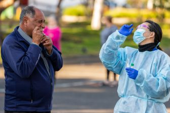 MELBOURNE, AUSTRALIA - JUNE 28: A man conducts a Covid-19 test by inserting a swab in his nose, under the guidance of a member of the Testing team during a COVID-19 testing blitz in the suburb of Broadmeadows on June 28, 2020 in Melbourne, Australia. Victoria's confirmed COVID-19 infection numbers continue to rise, with 49 new coronavirus cases recorded overnight. Health authorities are continuing on a testing blitz in Melbourne suburbs that have been identified as community transmission hotspots for coronavirus. Restrictions in Victoria have been tightened in response to the spike in new cases across the state with premier Daniel Andrews extending the current state of emergency for at least four weeks to allow police the power to enforce social distancing rules. (Photo by Asanka Ratnayake/Getty Images)