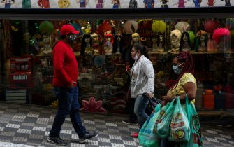 SAO PAULO, BRAZIL - JUNE 29: People wearing face masks walk in front of a shop in downtown  amidst the coronavirus (COVID-19) pandemic on June 29, 2020 in Sao Paulo, Brazil. The city of Sao Paulo moves to the Yellow phase of quarantine easing, in which commercial establishments can operate following distance rules such as reduced opening hours, restricting the flow of people and maintaining hygiene standards. (Photo by Alexandre Schneider/Getty Images)