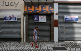 SAO PAULO, BRAZIL - JUNE 29: A man wearing a face mask walks in front of a shuttered shop with a 'For Lease' sign in downtown amidst the coronavirus (COVID-19) pandemic on June 29, 2020 in Sao Paulo, Brazil. Many businesses in the city of Sao Paulo went bankrupt and some commercial spaces are either for sale or for lease during the coronavirus (COVID-19) pandemic. (Photo by Alexandre Schneider/Getty Images)