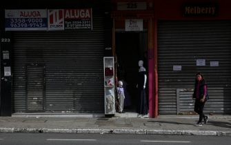 SAO PAULO, BRAZIL - JUNE 29: A woman wearing a face mask walks in front of a shuttered shop with a 'For Lease' sign in downtown amidst the coronavirus (COVID-19) pandemic on June 29, 2020 in Sao Paulo, Brazil. Many businesses in the city of Sao Paulo went bankrupt and some commercial spaces are either for sale or for lease during the coronavirus (COVID-19) pandemic. (Photo by Alexandre Schneider/Getty Images)