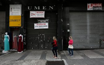 SAO PAULO, BRAZIL - JUNE 29: People wearing face masks walk in front of a shuttered shop with a 'For Lease' sign in downtown amidst the coronavirus (COVID-19) pandemic on June 29, 2020 in Sao Paulo, Brazil. Many businesses in the city of Sao Paulo went bankrupt and some commercial spaces are either for sale or for lease during the coronavirus (COVID-19) pandemic. (Photo by Alexandre Schneider/Getty Images)