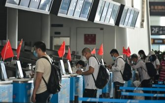 Passengers wearing face masks are seen at airline counters at Tianhe airport in Wuhan, in Chinas central Hubei province on May 23, 2020. - China took the rare move of not setting an annual growth target this year after the coronavirus battered the world's second-largest economy and ravaged global growth, Premier Li Keqiang said on May 22. (Photo by Hector RETAMAL / AFP) (Photo by HECTOR RETAMAL/AFP via Getty Images)