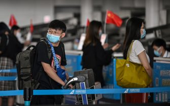 Passengers wearing face masks wait in line at an airline counter at Tianhe Airport in Wuhan, in Chinas central Hubei province on May 23, 2020. - China took the rare move of not setting an annual growth target this year after the coronavirus battered the world's second-largest economy and ravaged global growth, Premier Li Keqiang said on May 22. (Photo by Hector RETAMAL / AFP) (Photo by HECTOR RETAMAL/AFP via Getty Images)
