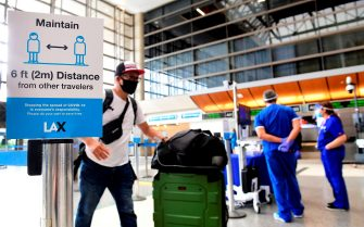 Passengers walks past thermal cameras, that check passenger's body temperatures, at Los Angeles International Airport in Los Angeles, California on June 23, 2020, after they were added as another layer of protection during the COVID-19 pandemic to help keep passengers safe. (Photo by Frederic J. BROWN / AFP) (Photo by FREDERIC J. BROWN/AFP via Getty Images)