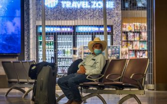 "A man seats in front of a closed newstand at LAX Airport at the start of the Memorial Day holiday weekend during the novel coronavirus, COVID-19, pandemic in  Los Angeles, California on May 22, 2020. - ""Last year, 43 million Americans traveled for Memorial Day Weekend  the second-highest travel volume on record since AAA began tracking holiday travel volumes in 2000,"" said Paula Twidale, senior vice president of AAA Travel. ""With social distancing guidelines still in practice, this holiday weekends travel volume is likely to set a record low."" (Photo by Apu GOMES / AFP) (Photo by APU GOMES/AFP via Getty Images)"