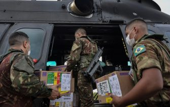 Members of the Brazilian Armed Forces load medical supplies at a military base in Boa Vista, to be taken to the Yanomamis indigenous lands of Auaris and Waikas, Roraima state, Brazil, on June 30, 2020, amid the novel coronavirus COVID-19 pandemic. (Photo by NELSON ALMEIDA / AFP) (Photo by NELSON ALMEIDA/AFP via Getty Images)