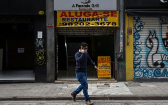 SAO PAULO, BRAZIL - JUNE 29: A man wearing a face mask walks in front of a shop with a 'For Lease' sign in downtown amidst the coronavirus (COVID-19) pandemic on June 29, 2020 in Sao Paulo, Brazil. Many businesses in the city of Sao Paulo went bankrupt and some commercial spaces are either for sale or for lease during the coronavirus (COVID-19) pandemic. (Photo by Alexandre Schneider/Getty Images)