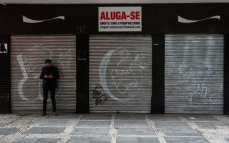 SAO PAULO, BRAZIL - JUNE 29: A man wearing a face mask stands in front of a shuttered shop with a 'For Lease' sign in downtown amidst the coronavirus (COVID-19) pandemic on June 29, 2020 in Sao Paulo, Brazil. Many businesses in the city of Sao Paulo went bankrupt and some commercial spaces are either for sale or for lease during the coronavirus (COVID-19) pandemic.  (Photo by Alexandre Schneider/Getty Images)