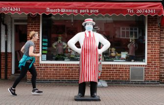 LEICESTER, ENGLAND - JULY 01: A woman runs past a masked mannequin stands outside a butchers shop in the Birstall area on July 01, 2020 in Leicester, England. Ten per cent of all the recent UKs Covid-19 deaths occurred in Leicester, which became the first British city to be put into regional lockdown on Tuesday night. (Photo by Darren Staples/Getty Images)