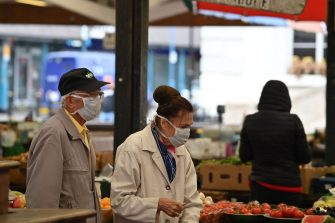 """Shoppers wearing PPE (personal protective equipment), of a face mask or covering as a precautionary measure against spreading COVID-19, choose produce at a farmers' mrketin the city centre of Leicester, central England, on June 30, 2020. - Britain on Monday reimposed lockdown measures on a city hit by an outbreak of coronavirus, in the first big test of Prime Minister Boris Johnson's """"whack-a-mole"""" strategy to control the disease while getting the economy moving again. (Photo by JUSTIN TALLIS / AFP) (Photo by JUSTIN TALLIS/AFP via Getty Images)"""