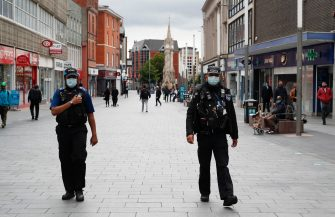 LEICESTER, ENGLAND - JULY 01: A police officer walks with a community  support officer during lockdown on July 01, 2020 in Leicester, England. Ten per cent of all the recent UKs Covid-19 deaths occurred in Leicester, which became the first British city to be put into regional lockdown on Tuesday night. (Photo by Darren Staples/Getty Images)