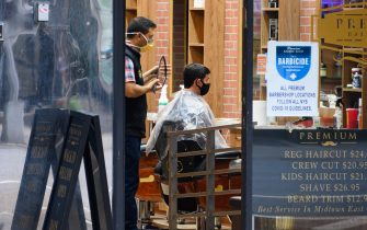 NEW YORK, NEW YORK - JUNE 30: A person wears a protective face mask while receiving a haircut in Murray Hill as New York City moves into Phase 2 of re-opening following restrictions imposed to curb the coronavirus pandemic on June 30, 2020. Phase 2 permits the reopening of offices, in-store retail, outdoor dining, barbers and beauty parlors and numerous other businesses. Phase 2 is the second of four phased stages designated by the state. (Photo by Noam Galai/Getty Images)