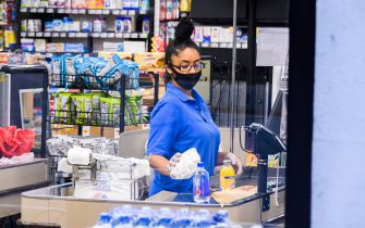 NEW YORK, NEW YORK - JUNE 30: A worker wears a face mask in Gristedes supermarket in Murray Hill as New York City moves into Phase 2 of re-opening following restrictions imposed to curb the coronavirus pandemic on June 30, 2020. Phase 2 permits the reopening of offices, in-store retail, outdoor dining, barbers and beauty parlors and numerous other businesses. Phase 2 is the second of four phased stages designated by the state. (Photo by Noam Galai/Getty Images)