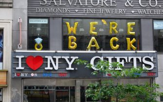 """NEW YORK, NEW YORK - JUNE 30: A """"we're back"""" sign is seen over the 'I Love NY' gift shop on the Upper East Side as New York City moves into Phase 2 of re-opening following restrictions imposed to curb the coronavirus pandemic on June 30, 2020. Phase 2 permits the reopening of offices, in-store retail, outdoor dining, barbers and beauty parlors and numerous other businesses. Phase 2 is the second of four phased stages designated by the state. (Photo by Noam Galai/Getty Images)"""