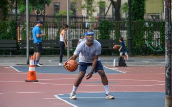 NEW YORK, NEW YORK - JUNE 30: A person plays basketball while wearing a face shield in Murray Hill as New York City moves into Phase 2 of re-opening following restrictions imposed to curb the coronavirus pandemic on June 30, 2020. Phase 2 permits the reopening of offices, in-store retail, outdoor dining, barbers and beauty parlors and numerous other businesses. Phase 2 is the second of four phased stages designated by the state. (Photo by Noam Galai/Getty Images)